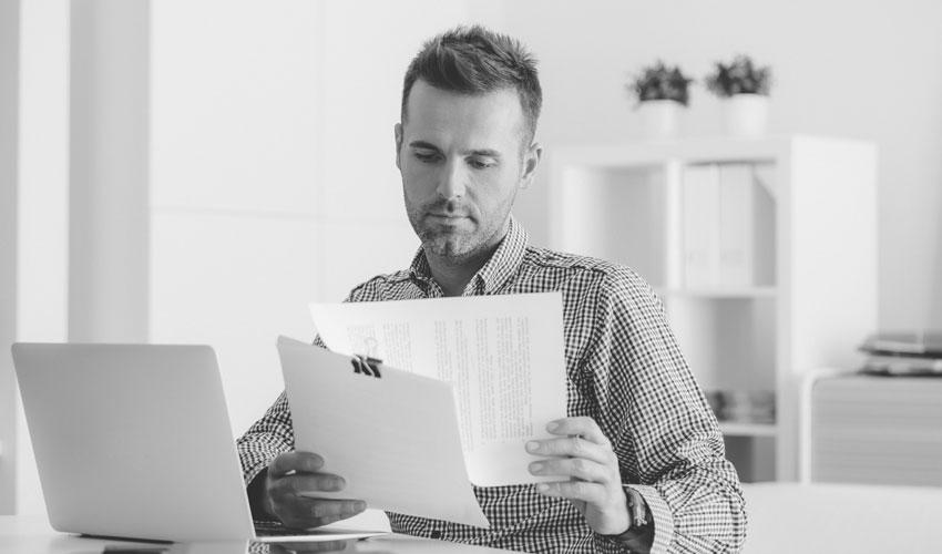 Bauingenieur sichtet Rechnungen für die Kostenfeststellung